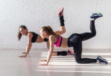 Две спортивные девушки выполняют сгибания ног на четвереньках для тренировки ягодиц