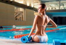 Красивая девушка в бассейне и белом купальнике