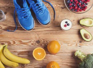 Пара голубых кросовак и здоровая пища на деревянном фоне