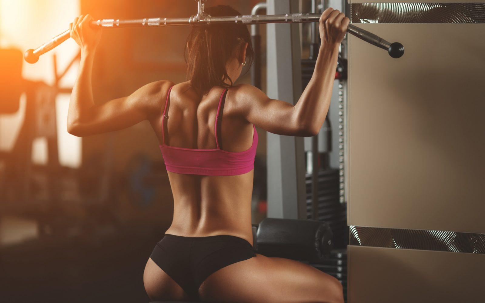 Спортивная девушка выполняет вертикальную тяга широким хватом из-за спины