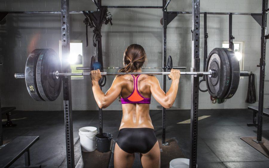 Спортивная девушка в тренажерном зале с тяжелой штангой на плечах