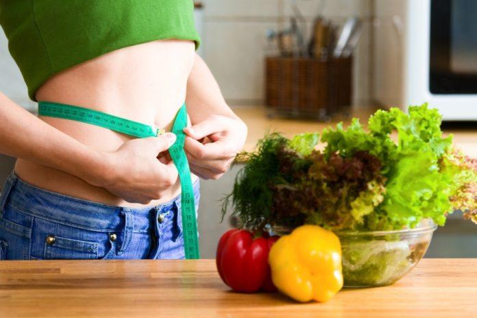 Стройная девушка на кухне измеряет талию