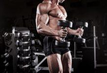 Мускулистый атлет в тренажерном зале с гантелями