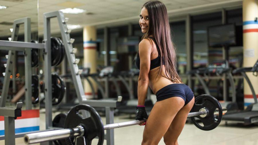 Красивая девушка в тренажерном зале со штангой