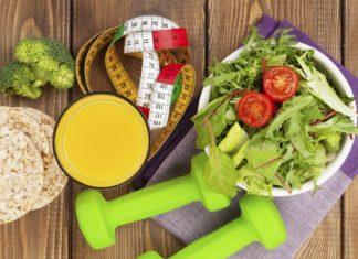 Гантели, сок, салат, хлебцы, сантиметровая лента на деревянном столе