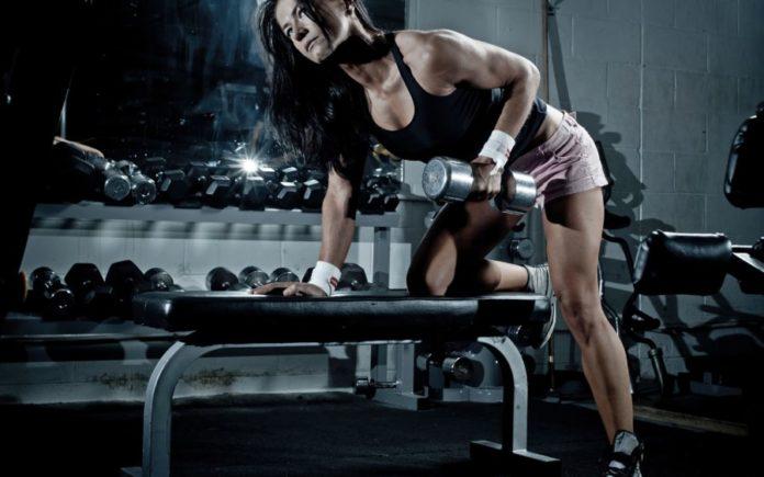 Спортивная девушка выполняет тягу гантелей в наклоне (на широчайшие мышцы)