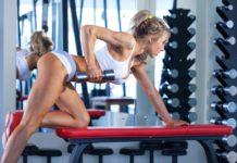 Спортивная девушка выполняет упражнения в тренажерном зале: тяга гантели к поясу в наклоне