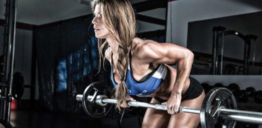 Тяга в наклоне обратным хватом в тренажерном зале в исполнении спортивной девушкой
