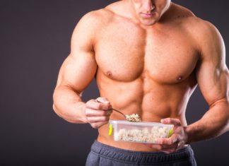 Накаченный парень кушает рис из пищевого контейнера