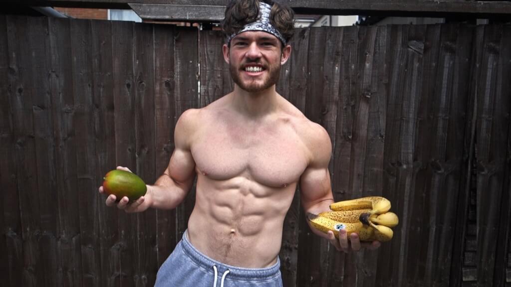 Подкаченный атлет в шортах держин в руках авокадо и бананы