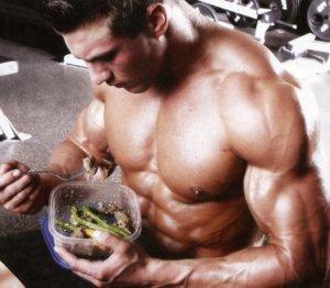 Мускулистый парень кушает из пищевого контейнера
