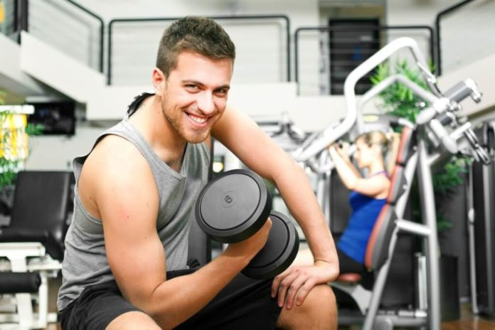 Начинающий атлет в тренажерном зале с гантелью в руке