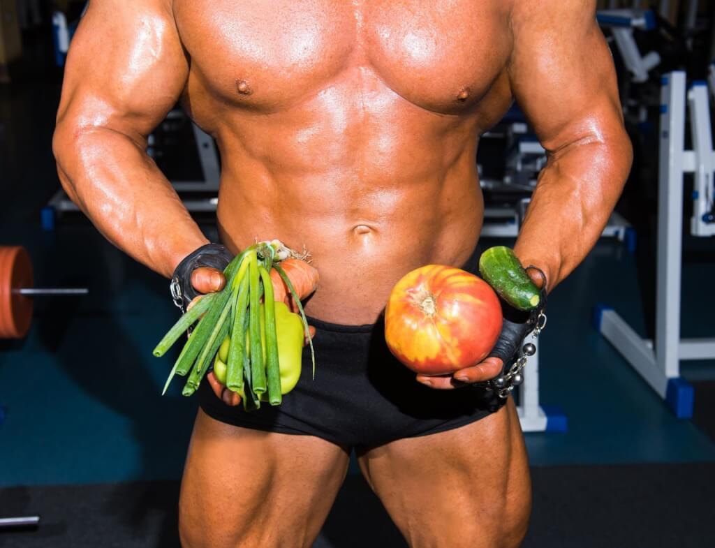 Бодибилдер с овощами и фруктами в руках