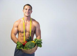 Атлет с голым торсом держит в руках корзину с овощами