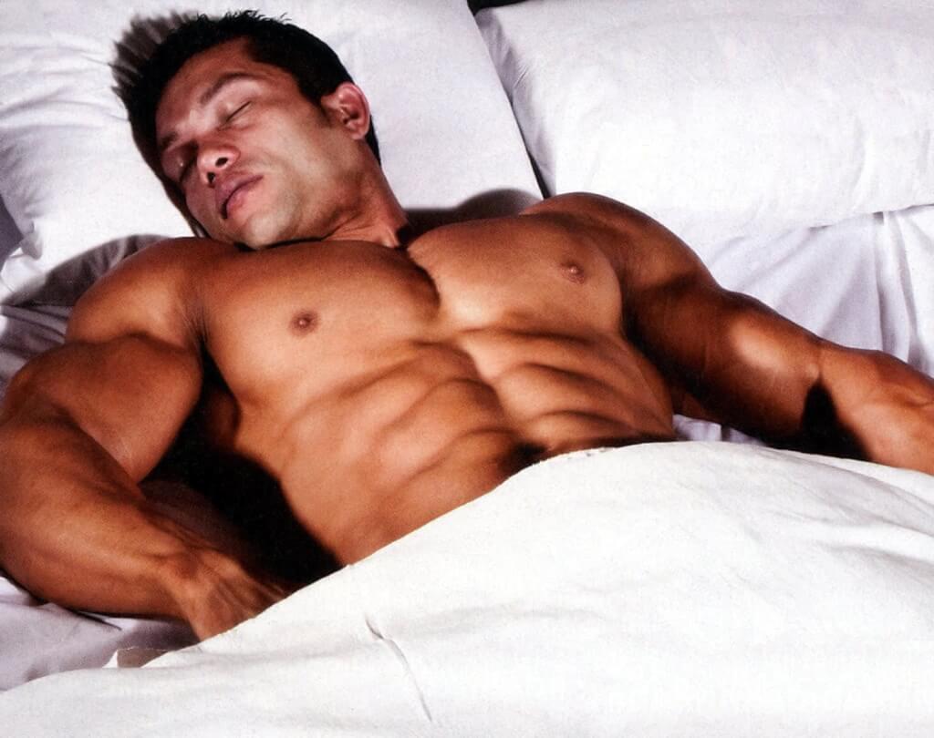 Накаченный мужчина спит в белой кровати