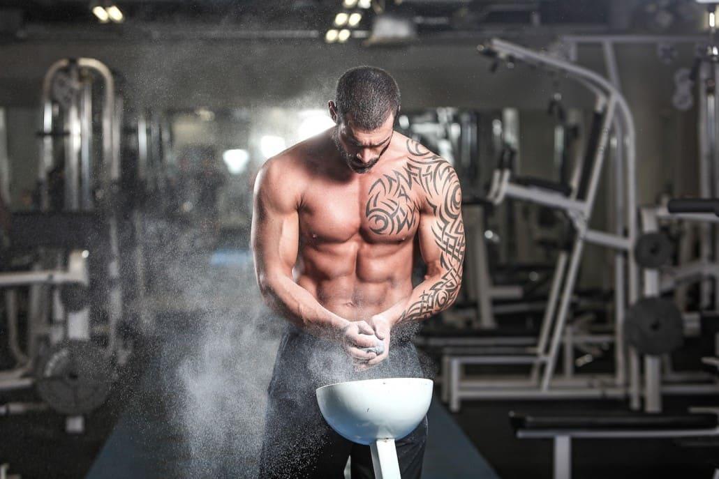 Спортсмен в тренажерном зале посыпает ладони магнезией