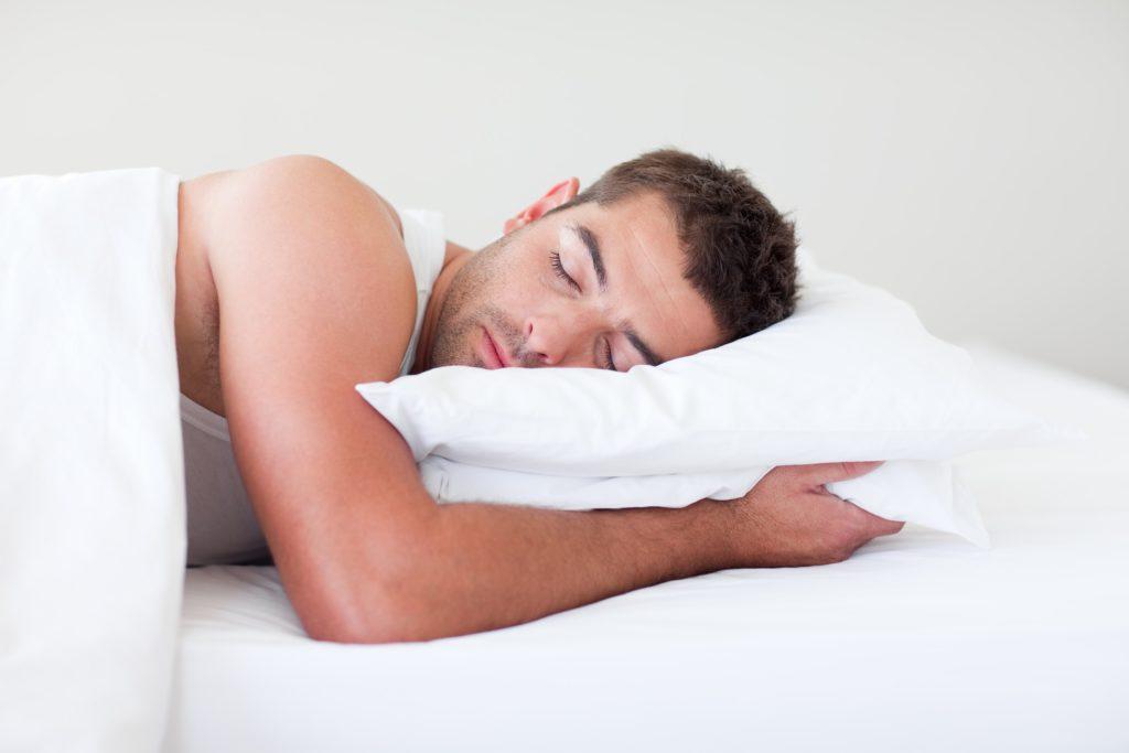 Человек спит на белой подушки в кровати