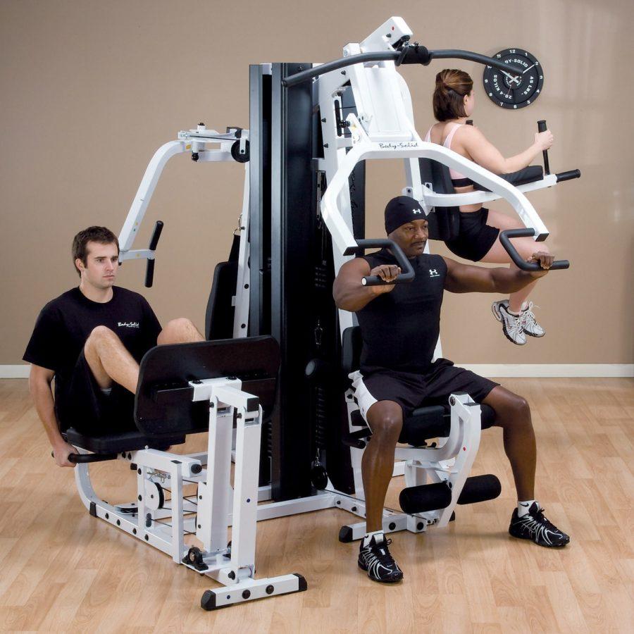 Два мужчины тренируются на одном комплексном силовом тренажере