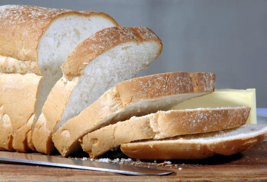 Нарезанная буханка белого хлеба и нож на столе
