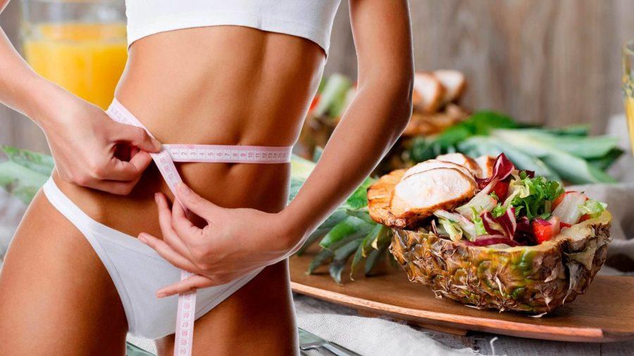 Стройная девушка с сантиметровой лентой на фоне продуктов питания