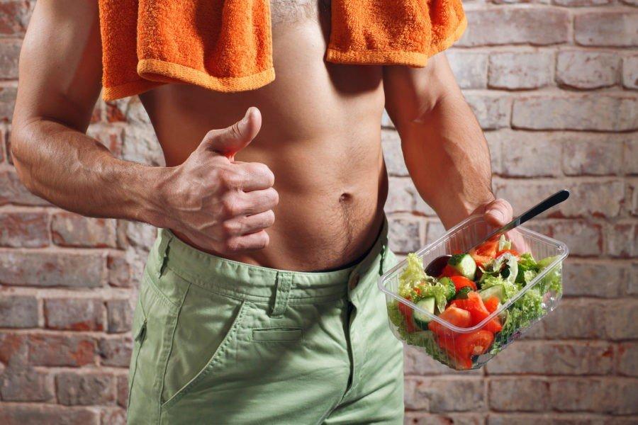 Атлет с голым торсом, держит контейнер с овощным салатом