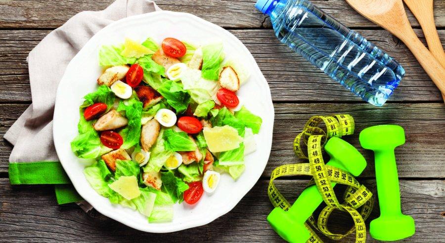 Фитнес салат, сантиметровая лента и гантеля на деревянном фоне