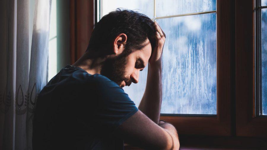 Грустный человек возле окна