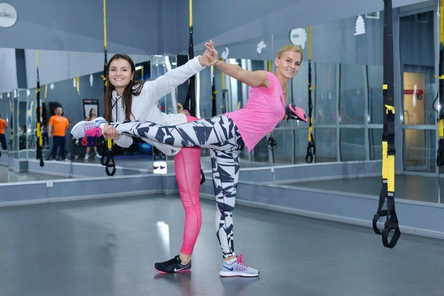 Две спортивные веселые девушки в спортзале с поднятыми ногами