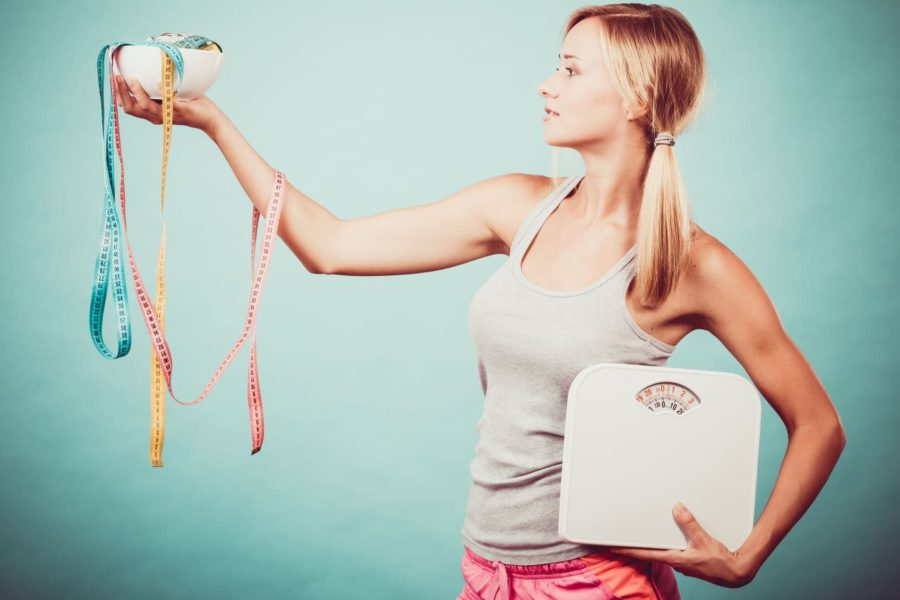 Стройная девушка с весами наполнами держит сантиментровую ленту