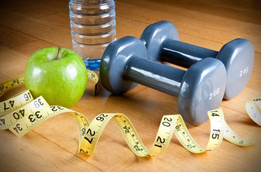 Зеленное яблоко, гантель, сантиметровая лента и бутылка воды