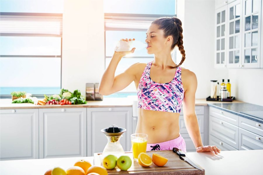 Стройная девушка на кухне пьет сок и фрукты на столе