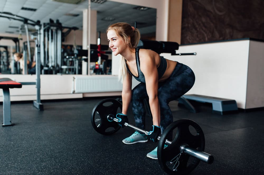 Девушка в тренажерном зале выполняет становую тягу с узкой постоновкой ног