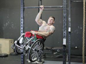 Инвалид-колясочник подтягивается на одной руке держась за турник в спортивном зале