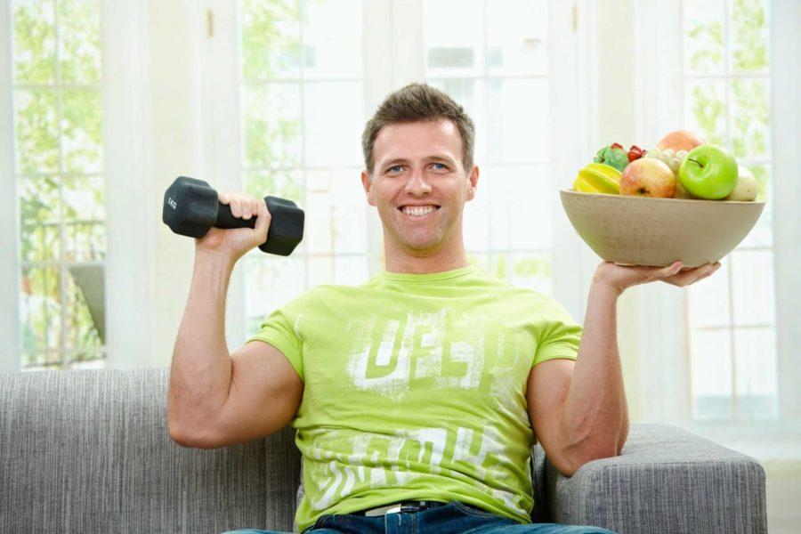 Мужчина на диване держит водной руке гантелю, в другой блюдце с фруктами