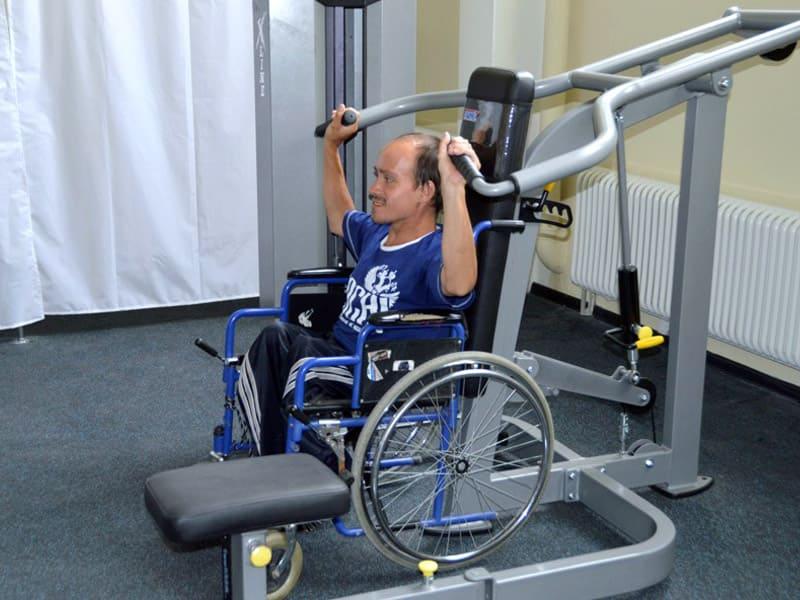 Инвалид-колясочник тренирует плечи