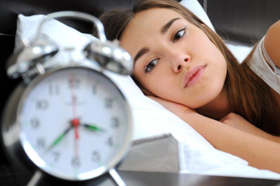 Девушка на постели и будильник