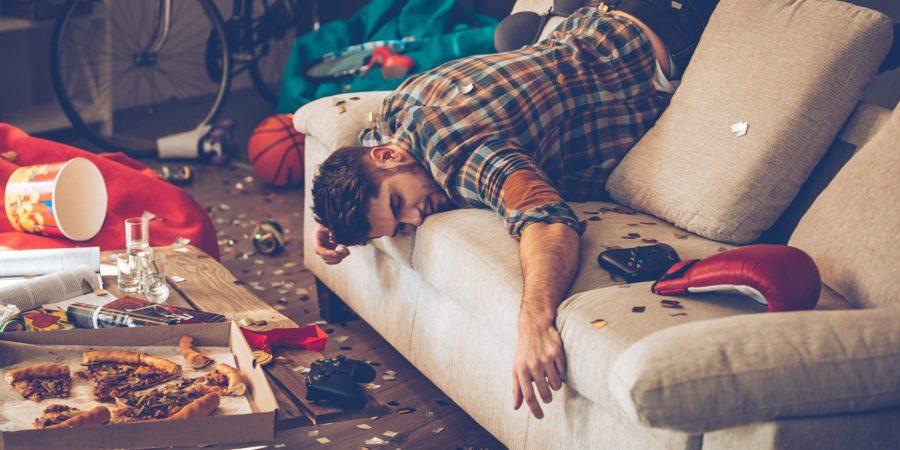 Мужчина бездельник валяется на диване в грязной комнате