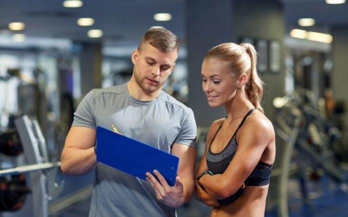 Тренер инструктирует девушку в тренажерном зале
