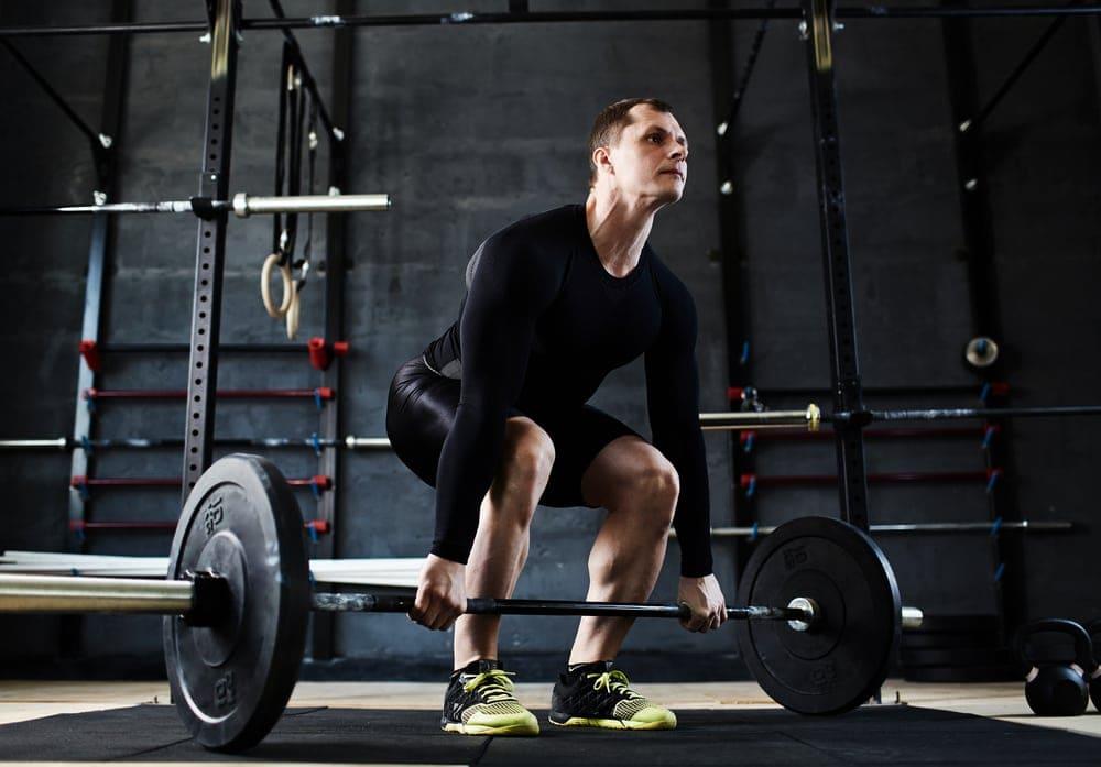 Парень выполняет становую тягу с узкой постановкой ног