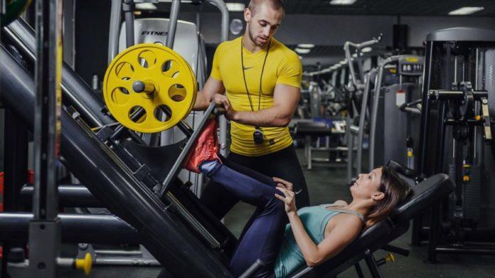 Девушка выполняет упражнение - жим ногами в тренажере