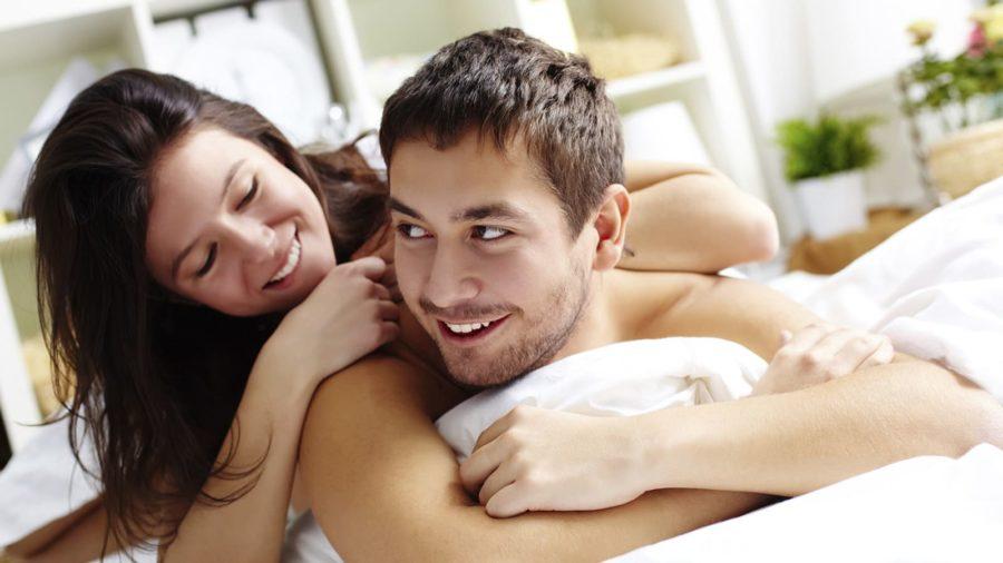 Радостные парень и девушка лежат в обнимку в одной постели