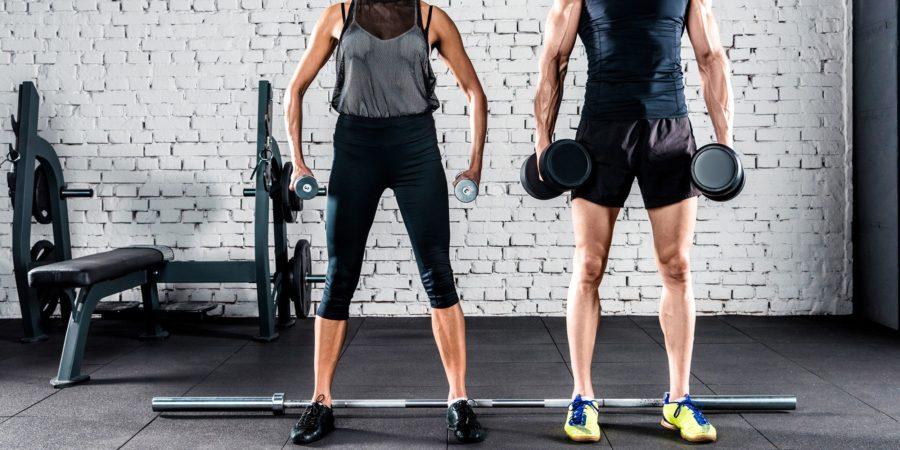 Парень и девушка проводят совместную тренировку с гантелями в руках