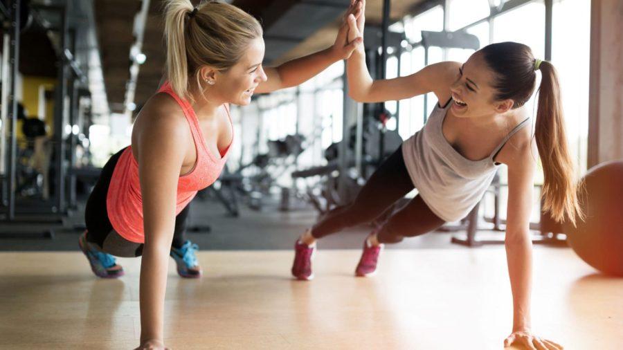 Две радостные девушки держаться за руки в тренажерном зале