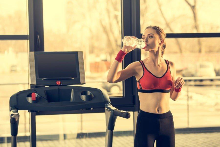 Спортивная девушка пьет воду возле беговой дорожке