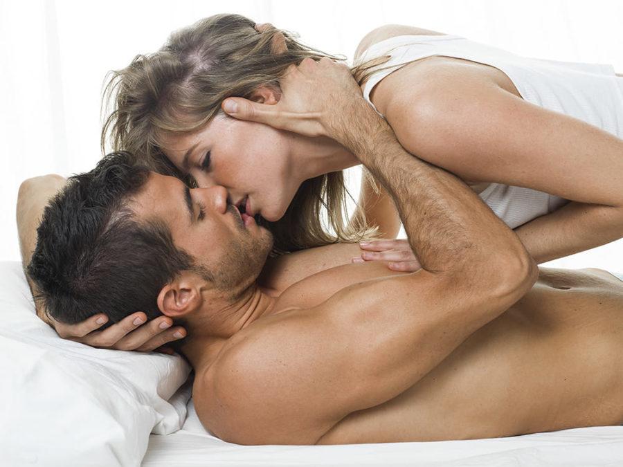 Парень страстно целуется с девушкой на белой постели