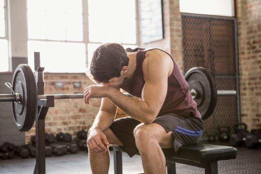Уставший спортивный парень сидит на скамье в тренажерном зале