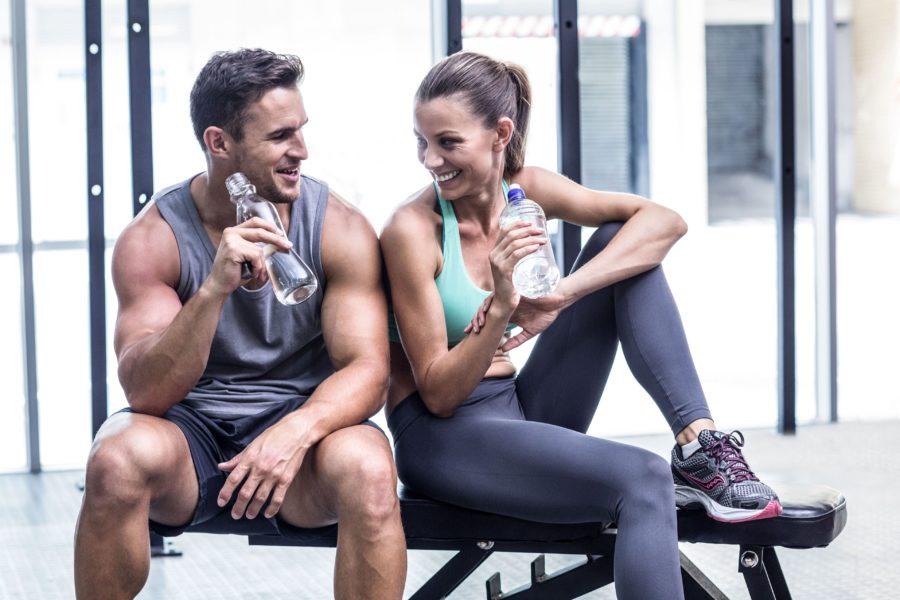 Парень и девушка мило беседуют сидя на скамье в тренажерном зале