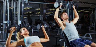 Парень и девушка в тренажерном зале выполняют силовые упражнения на плечи