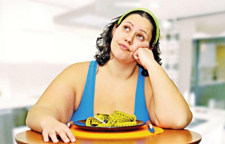 Полная девушка смотрит в потолок за столом с тарелкой еды