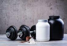 Банки спортивного питания, гантели и чарпак с протеином на фоне текстуры